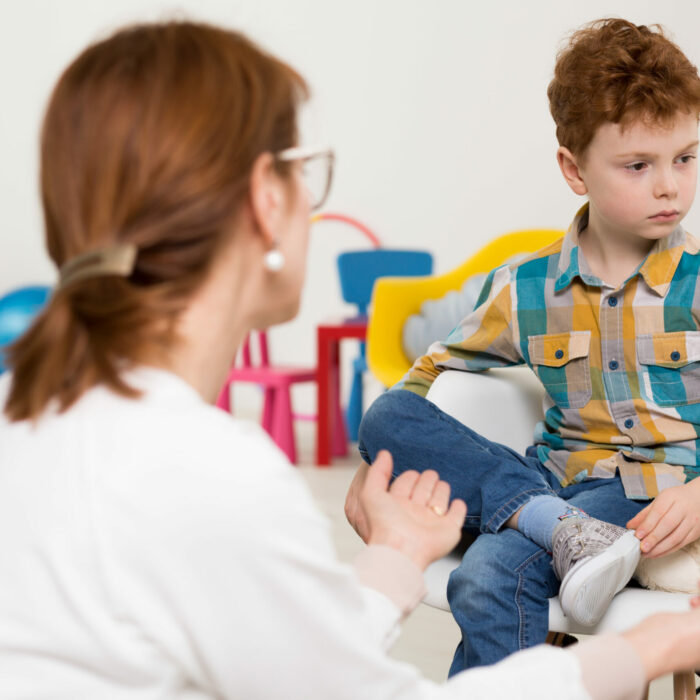 Little boy at a therapist's office, sitting in a white chair in front of his psychologist in a rebellious manner